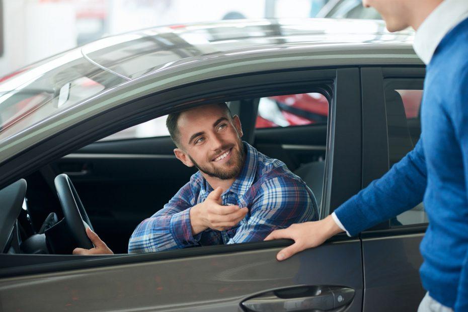 Car seller and customer handshake in car dealership