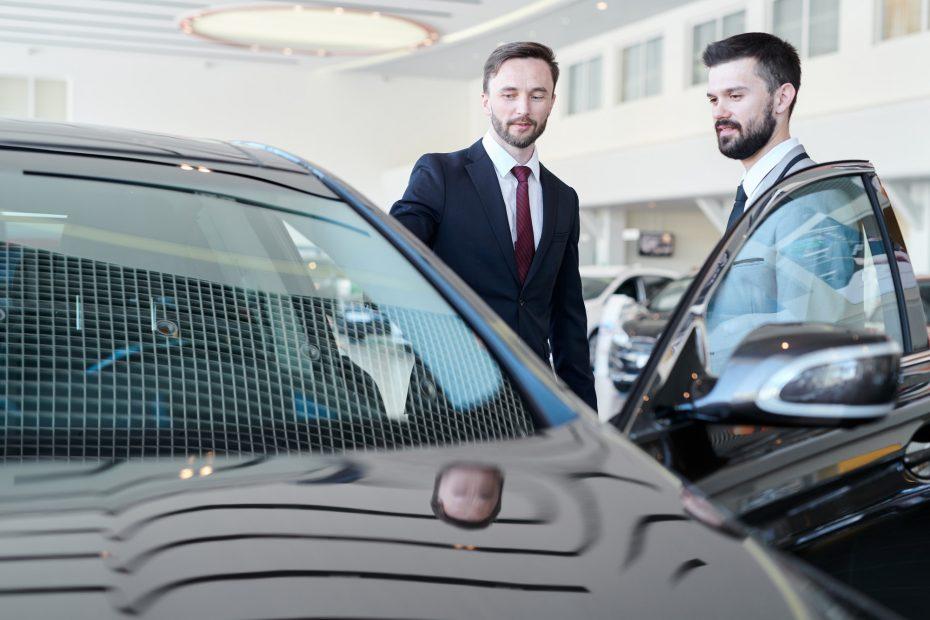 Man choosing a car with car dealer